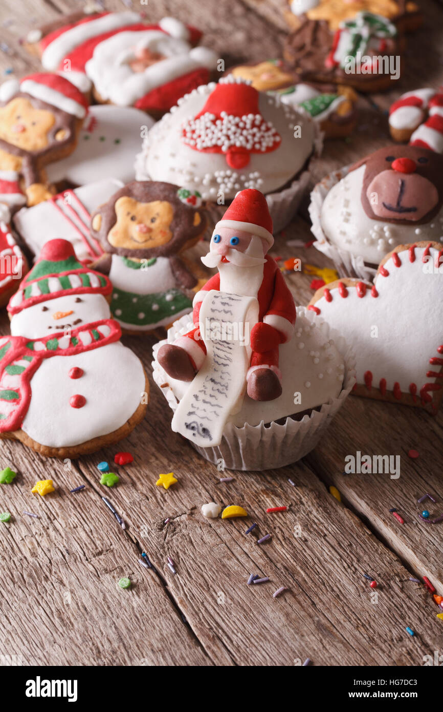 Christmas cupcakes and gingerbread cookies close-up on a wooden table. vertical - Stock Image