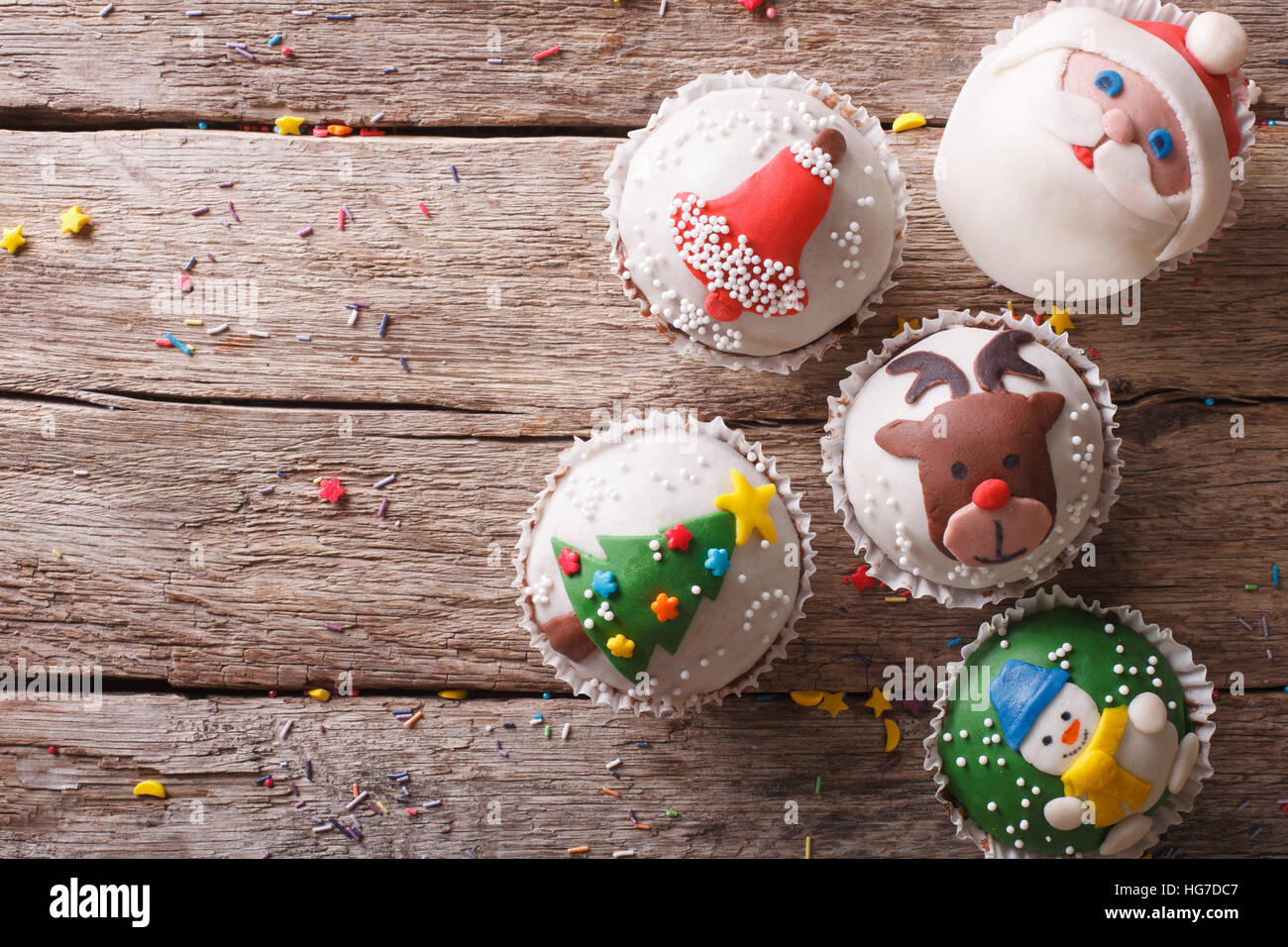 Christmas sweets: cupcakes closeup on a wooden table. horizontal top view - Stock Image