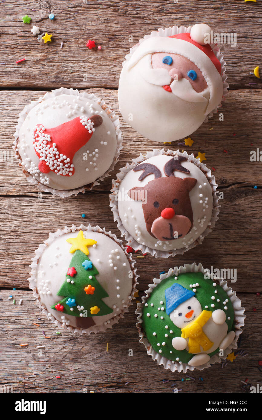 Christmas sweets: cupcakes closeup on a wooden table. vertical top view - Stock Image