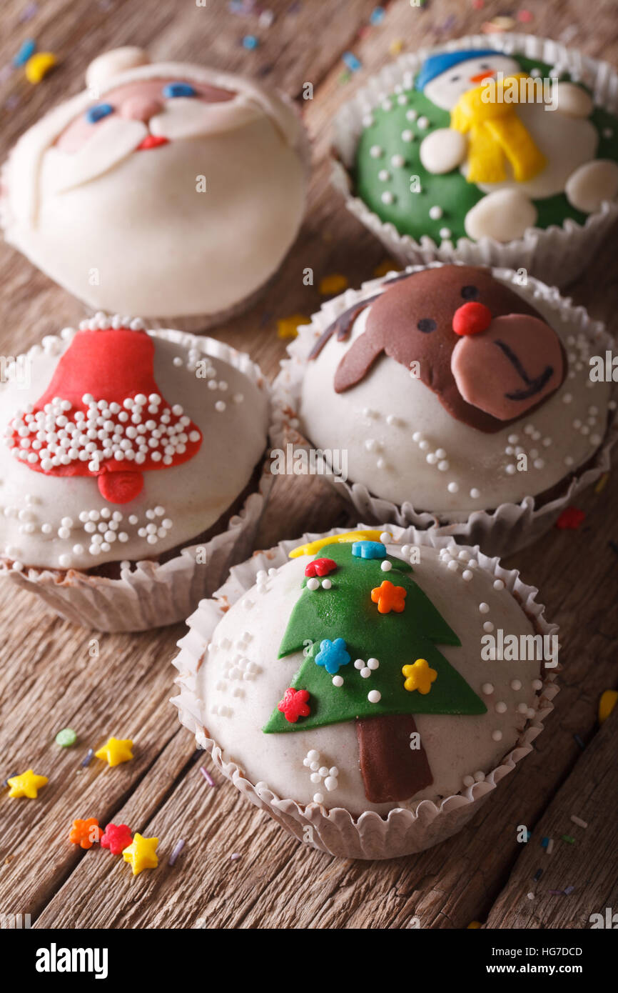 Beautiful festive cupcakes with Christmas decorations close-up on a wooden table. Vertical - Stock Image