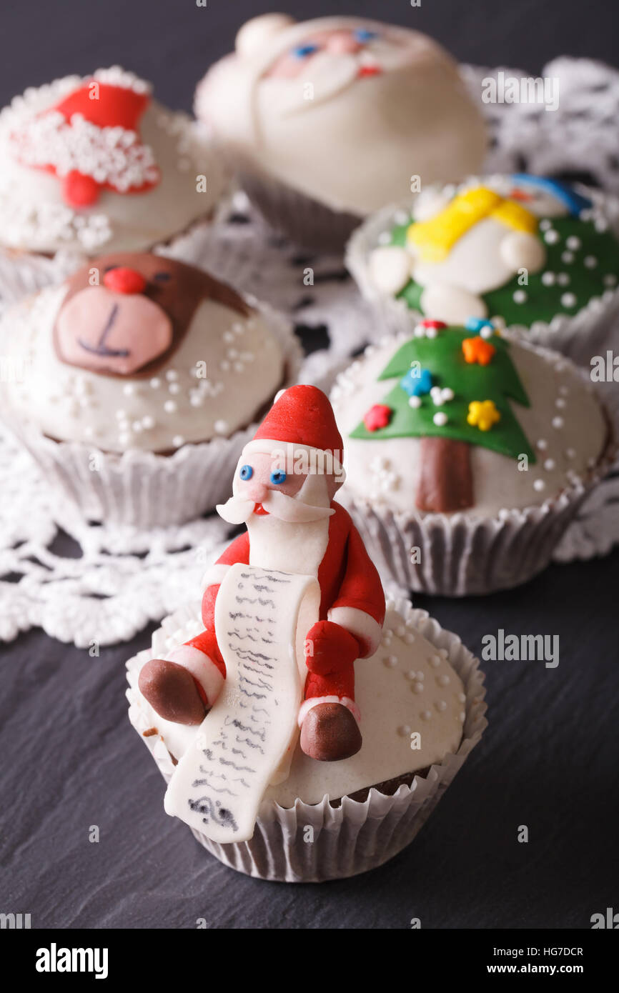 Beautiful delicious cupcakes with Christmas decorations close-up. vertical - Stock Image