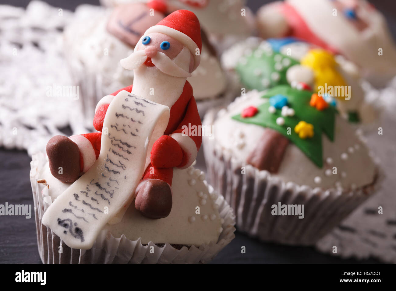 Christmas cupcakes decorated with the figure of Santa macro on the table. horizontal - Stock Image