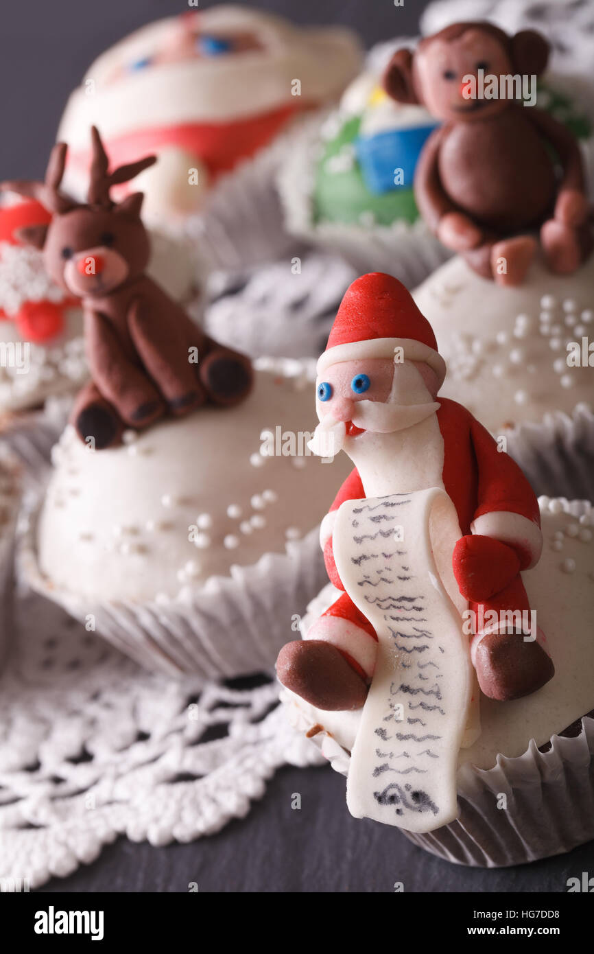 Beautiful Christmas cupcakes decorated with the figure of Santa macro on the table. vertical - Stock Image