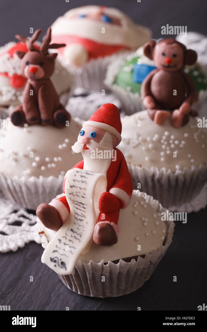 Christmas cupcakes decorated with the figure of Santa close-up on the table. vertical - Stock Image
