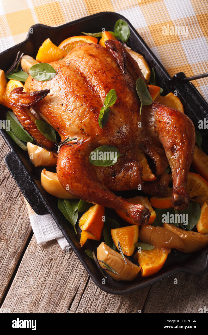Delicious roast chicken with oranges and apples close-up in a pan. vertical - Stock Image