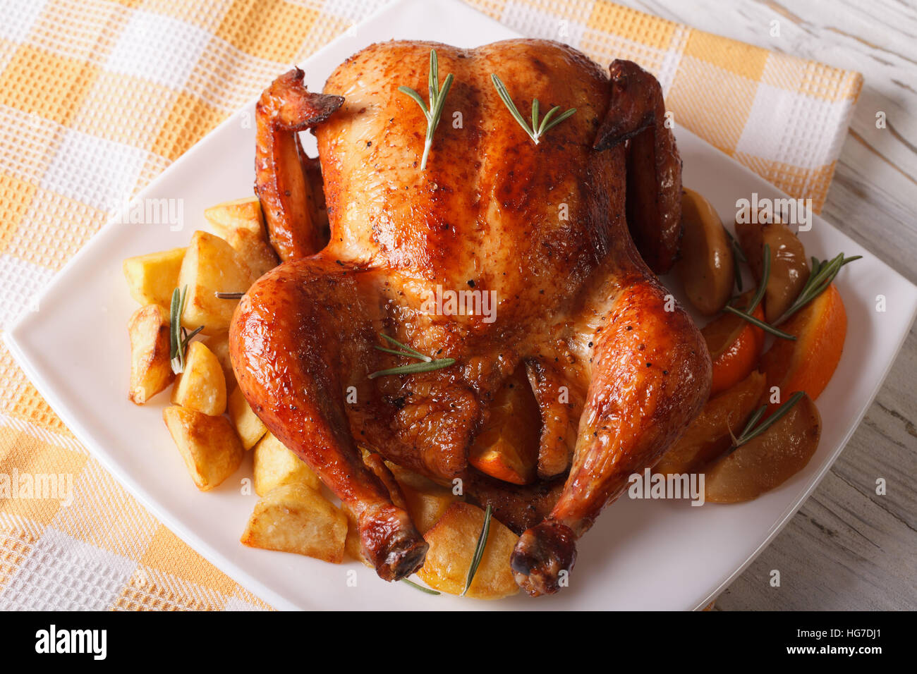 whole roast chicken with oranges, potatoes and apples close-up on a plate. horizontal - Stock Image