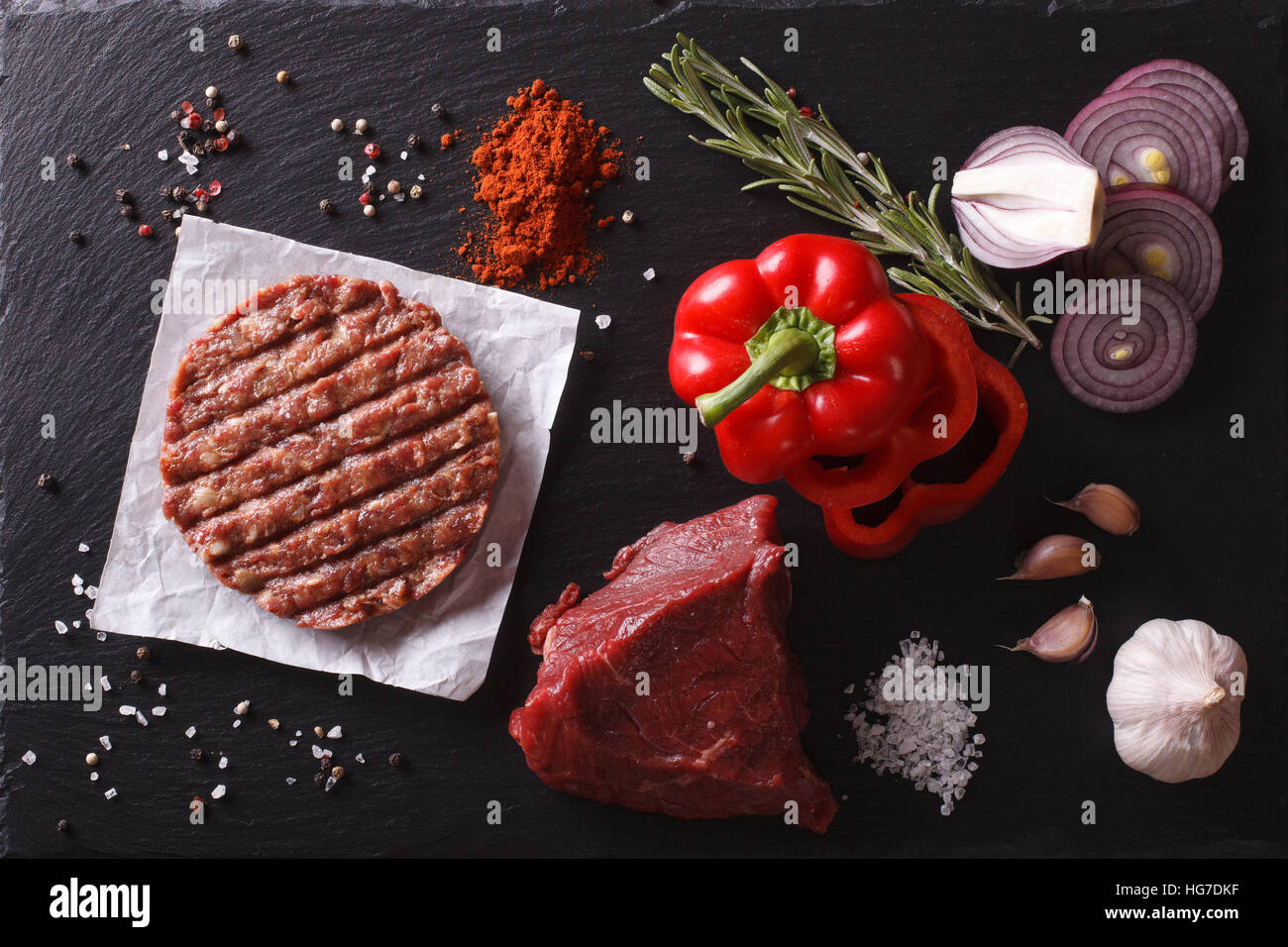 Raw Ground beef meat Burger steak cutlets with ingredients on the board. horizontal view from above closeup - Stock Image