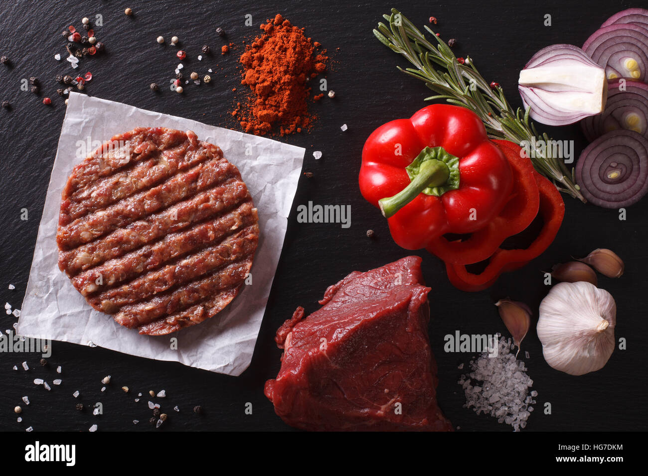 Raw Ground beef meat Burger steak cutlets with ingredients on the board. horizontal view from above - Stock Image
