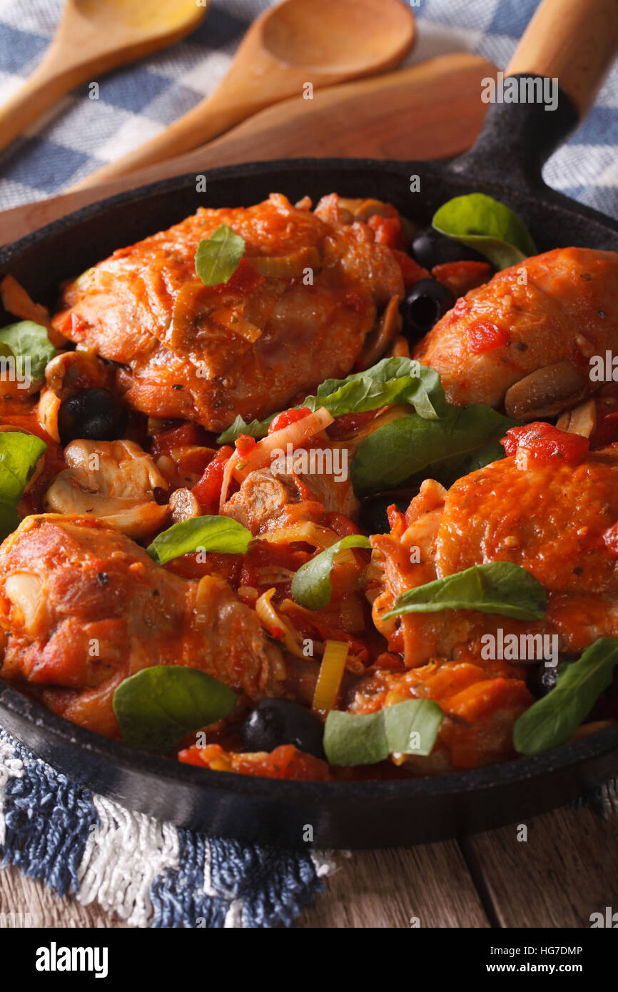 Italian food: chicken with tomato and vegetables close-up in a frying pan. Vertical - Stock Image