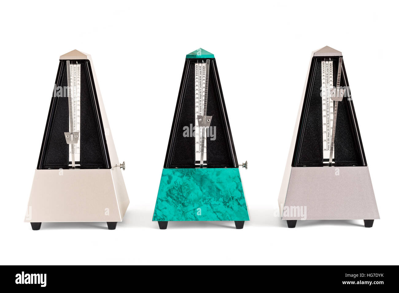 Three pyramid shaped metronomes in plastic housing isolated on white - Stock Image