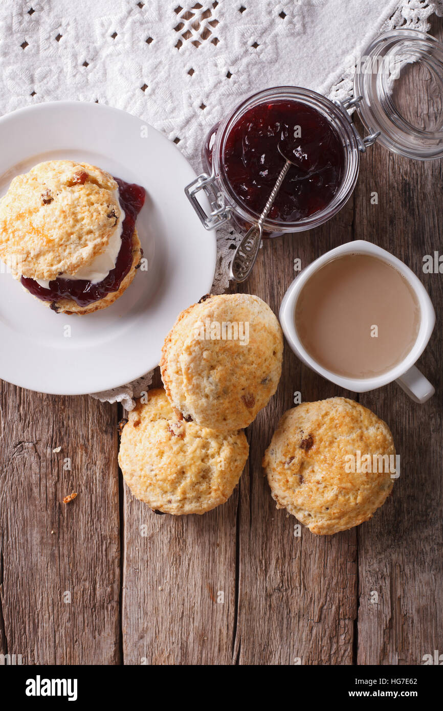 Delicious English scones with jam and tea with milk on the table. vertical top view - Stock Image