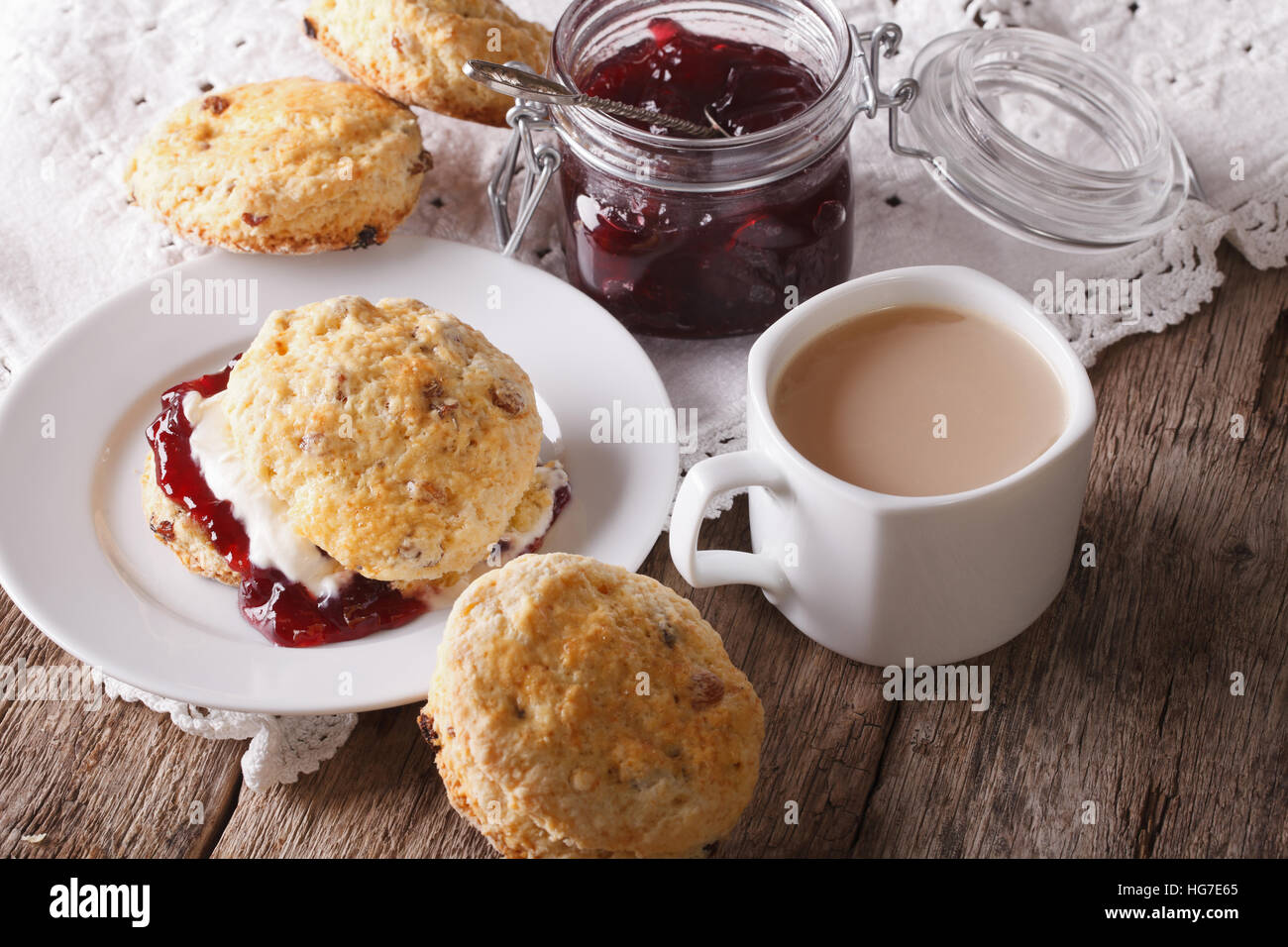 Homemade buns with jam and tea with milk close-up on the table. horizontal - Stock Image
