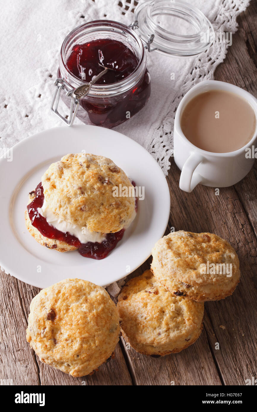 Homemade buns with jam and tea with milk close-up on the table. Vertical - Stock Image