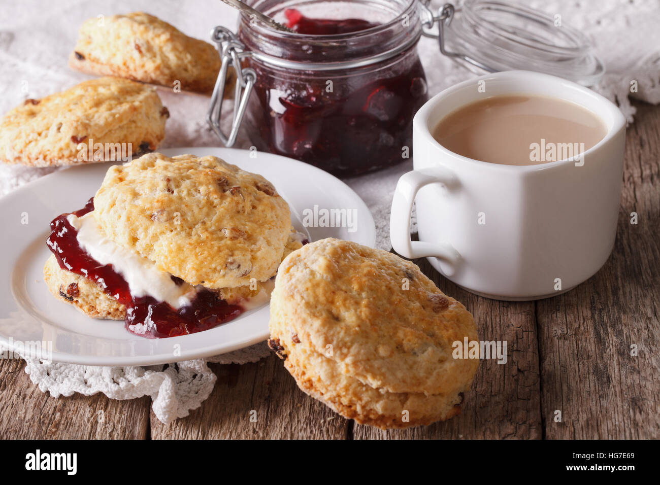 Scones with jam and tea with milk close-up on the table. horizontal - Stock Image