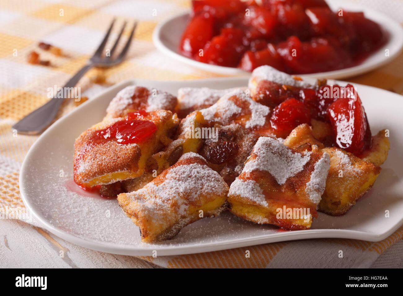Austrian dessert Kaiserschmarrn with plum sauce close-up on a plate. horizontal Stock Photo