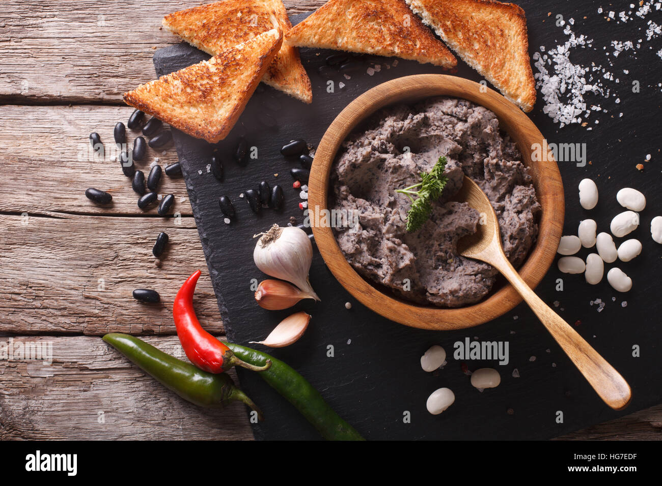Frijoles refritos with ingredients on a table close-up. horizontal view from above - Stock Image