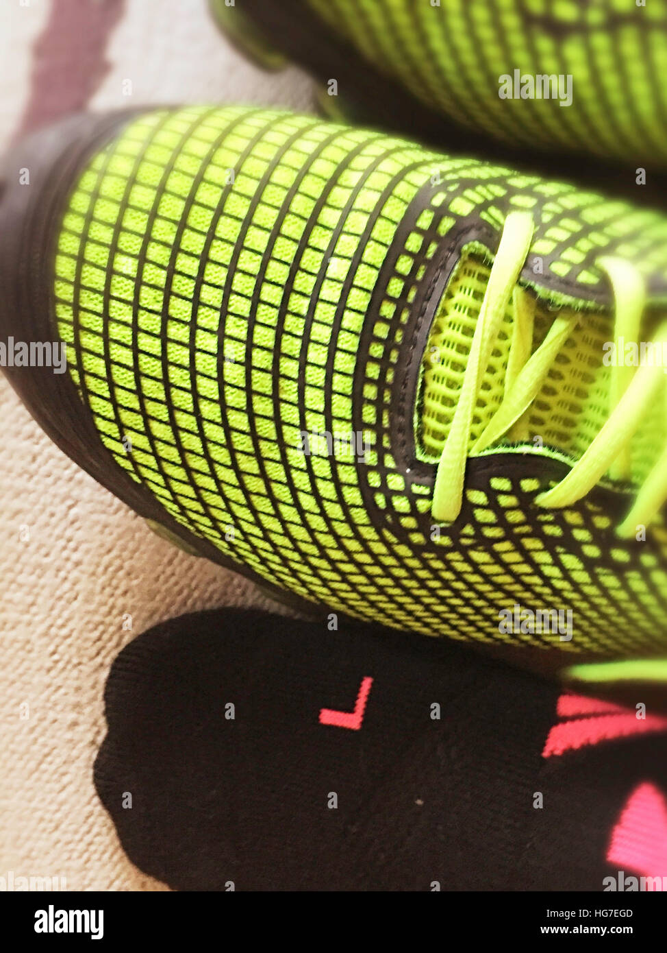 Bright Neon Green Running Shoes with Compression Sock fro Left Foot - Stock Image