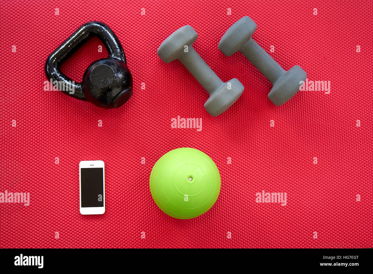 Gym equipment on red mat background, top view - Stock Image