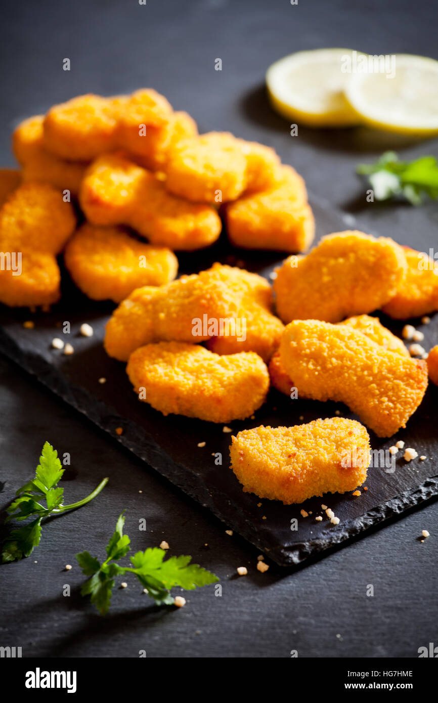 Bunch of tasty chicken nuggets on a slate plate - Stock Image