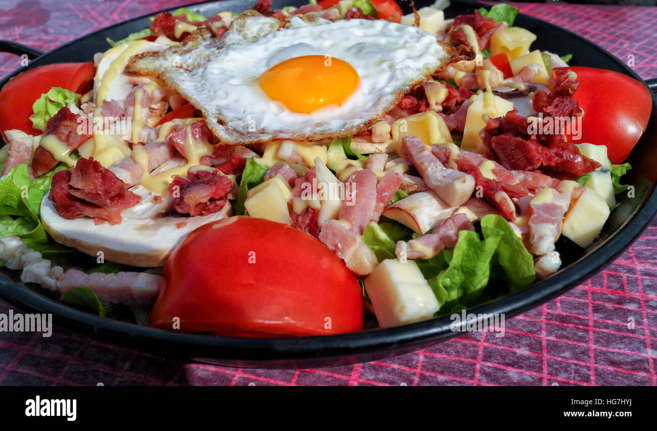 Plate of fried egg, chunks of bacon, sausage, cheese served with red tomato and lettuce - Stock Image