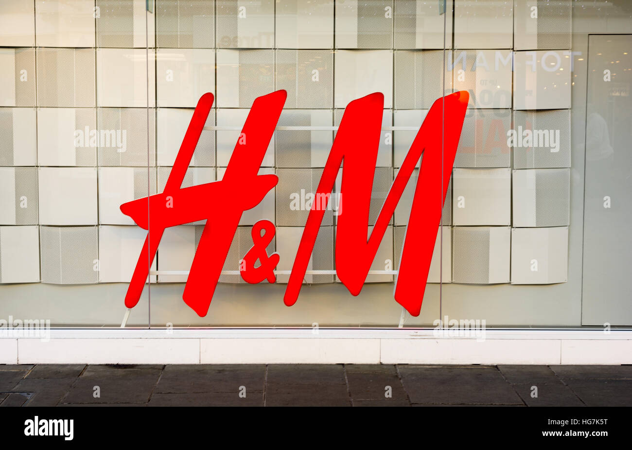 The logo of H&M, the Swedish fashion retailer, displayed large in a shop window. - Stock Image