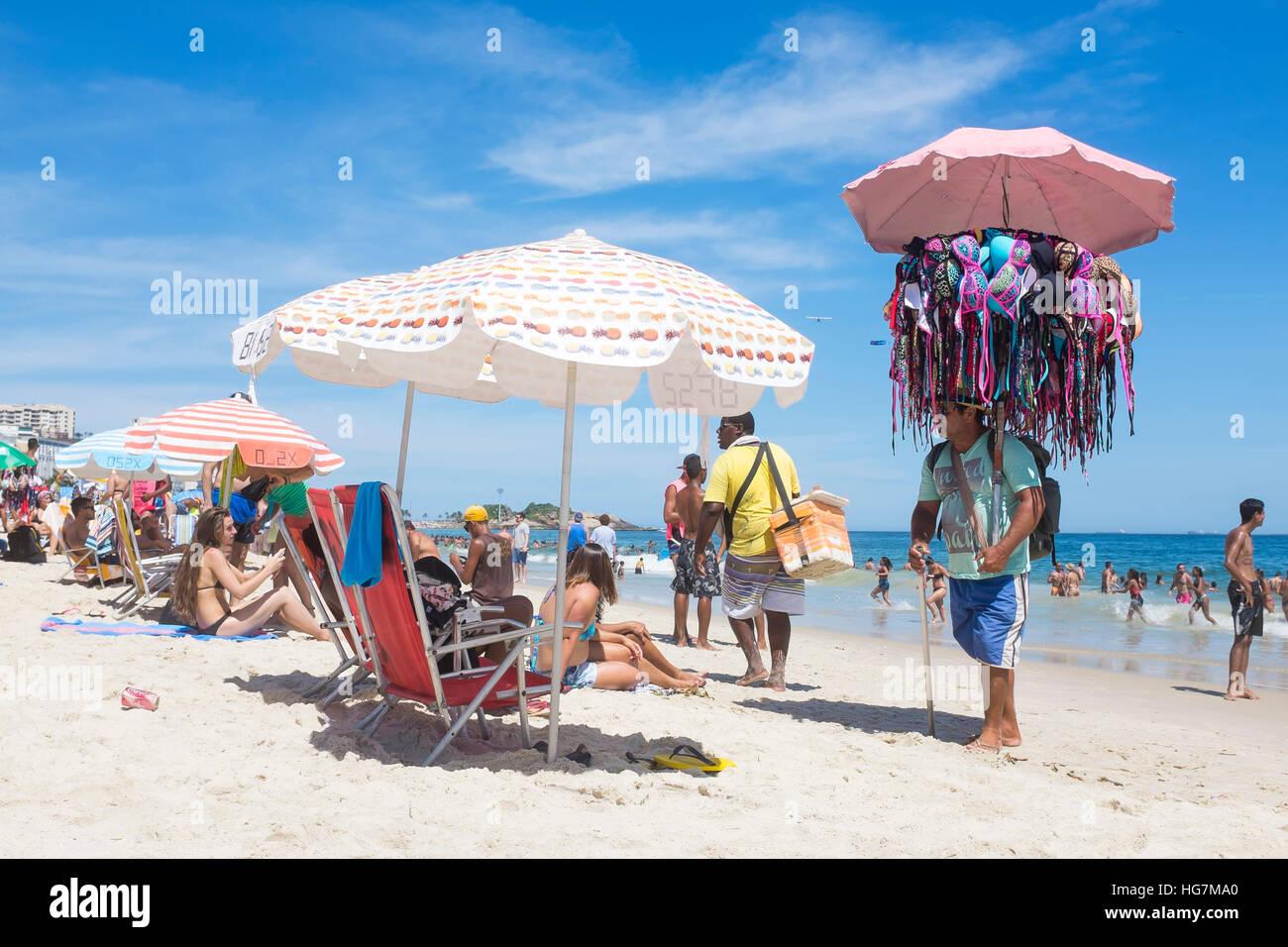 RIO DE JANEIRO - JANUARY 05, 2016: Beach vendors and sunbathers share a bright day on Ipanema Beach. - Stock Image
