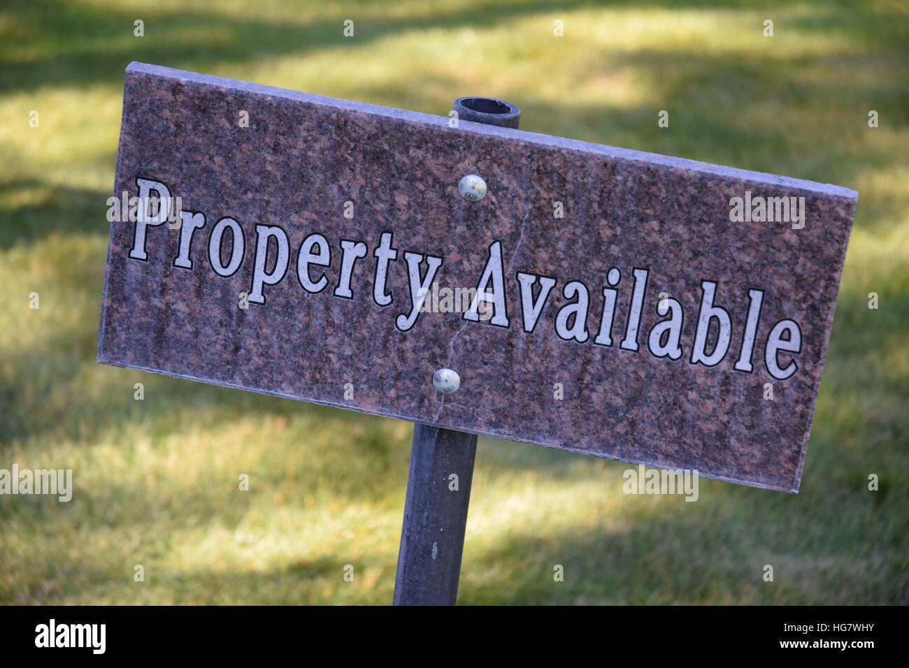Property Available sign in cemetery. - Stock Image