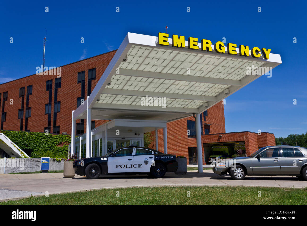 Yellow Emergency Sign with Police Car Near Entrance IX - Stock Image
