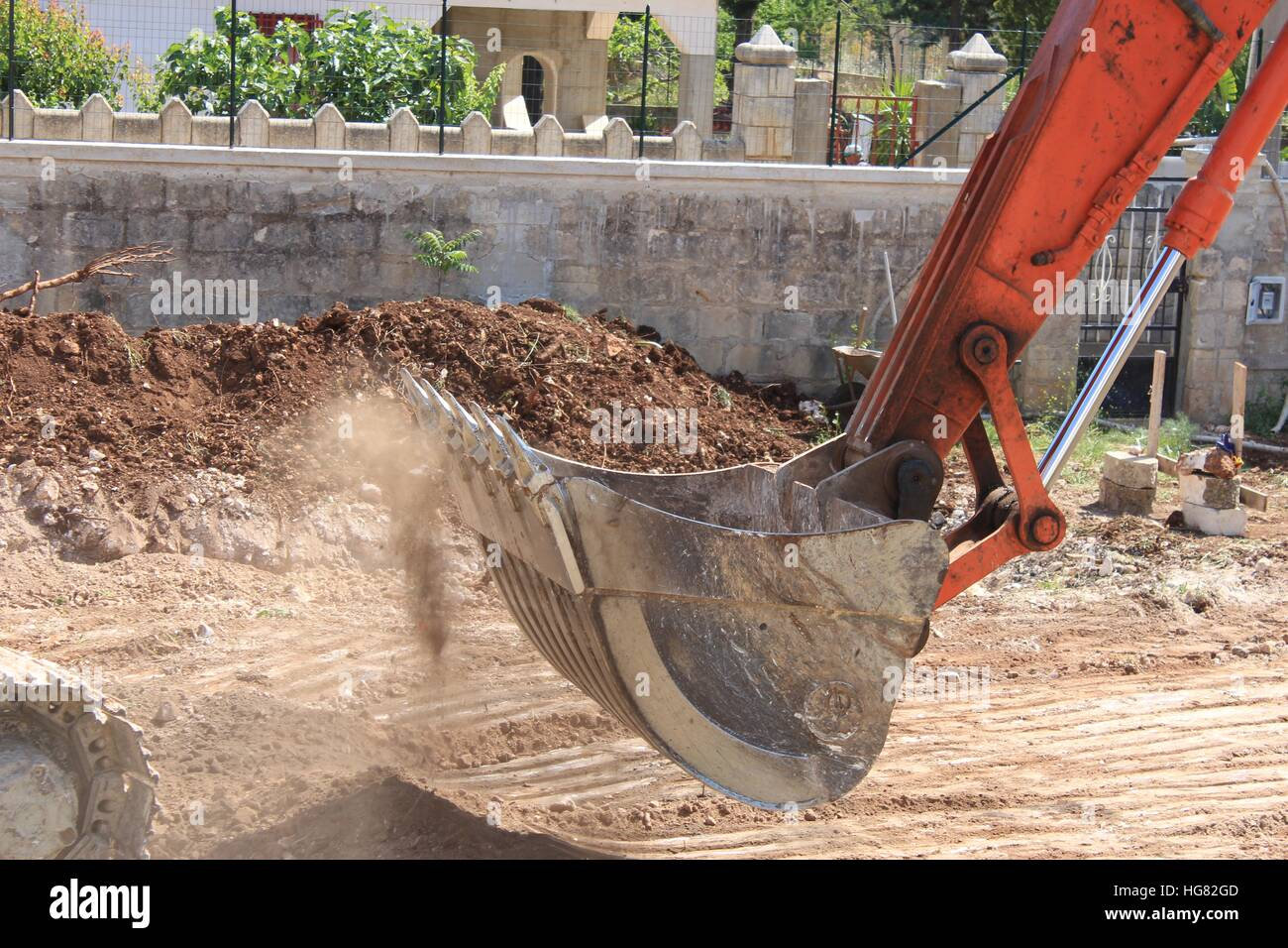 The bucket of a back hoe machine smooths dry earth into place. - Stock Image