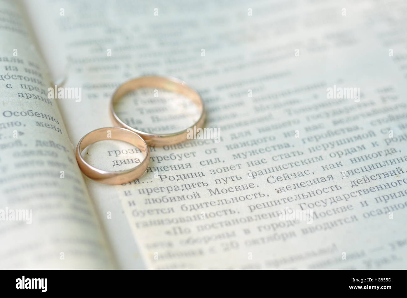 Wedding rings forming a heart onto a book - Stock Image