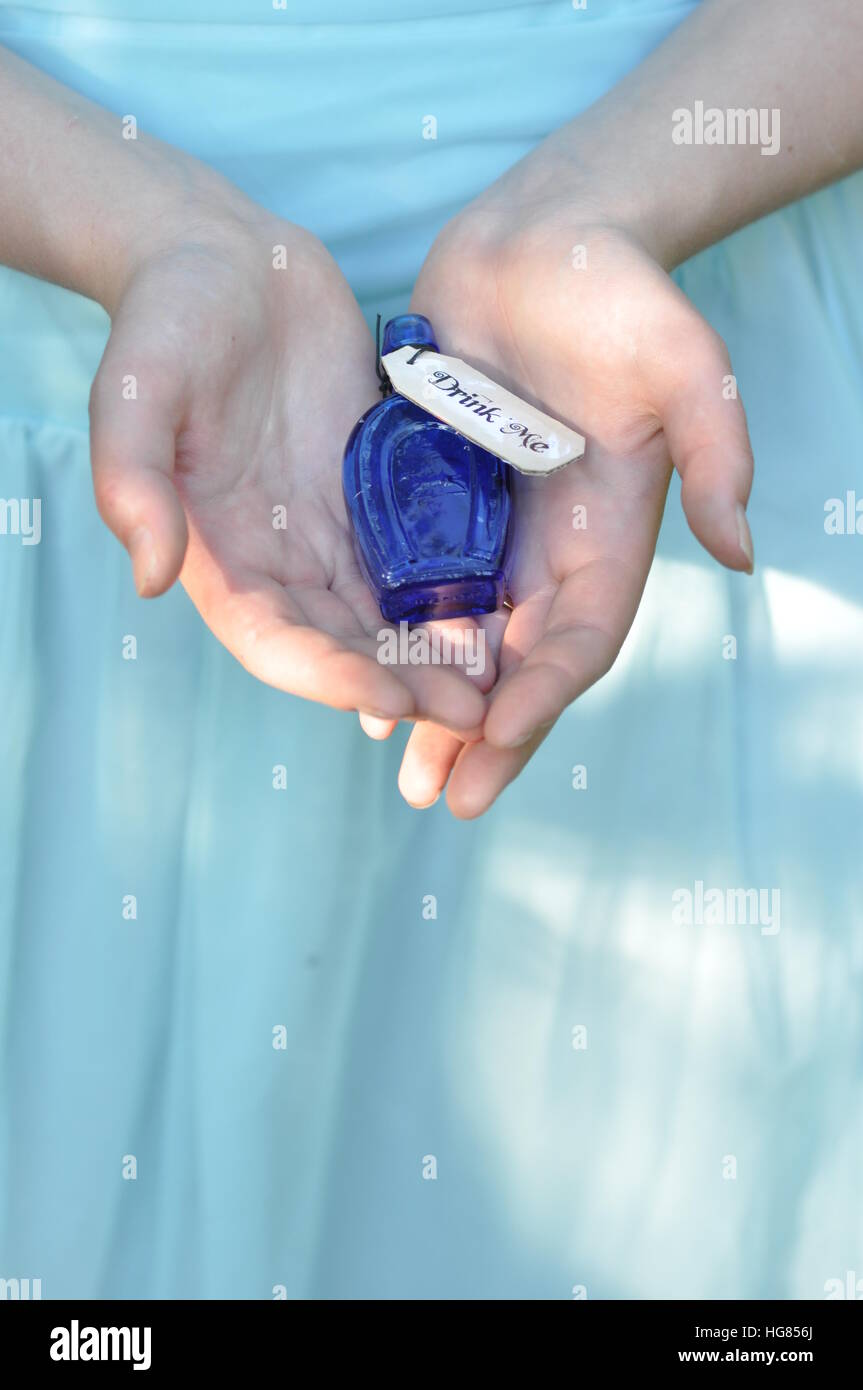 Drink me bottle. Hand holding bottle. - Stock Image