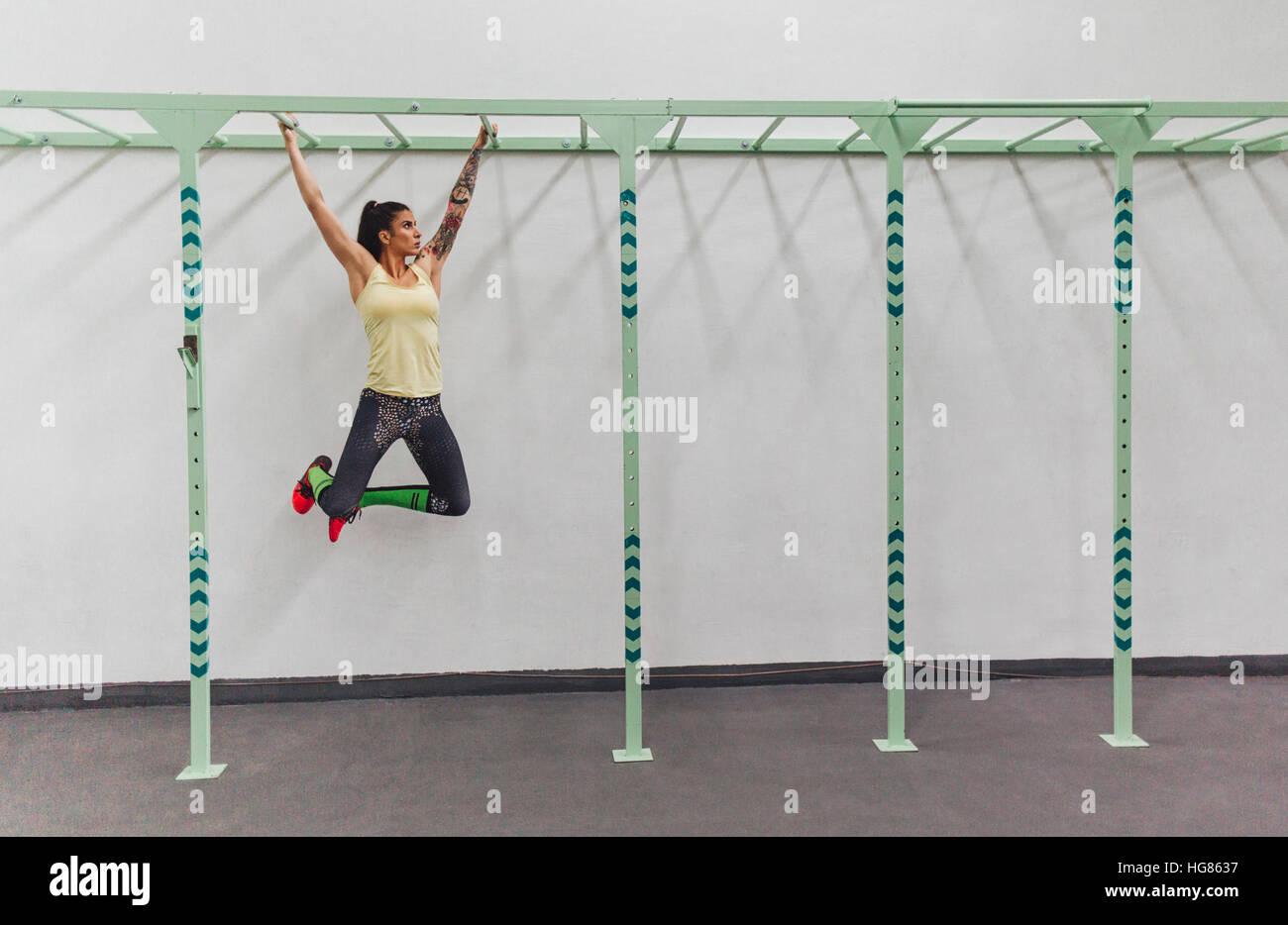 Athlete hanging on monkey bars in gym - Stock Image