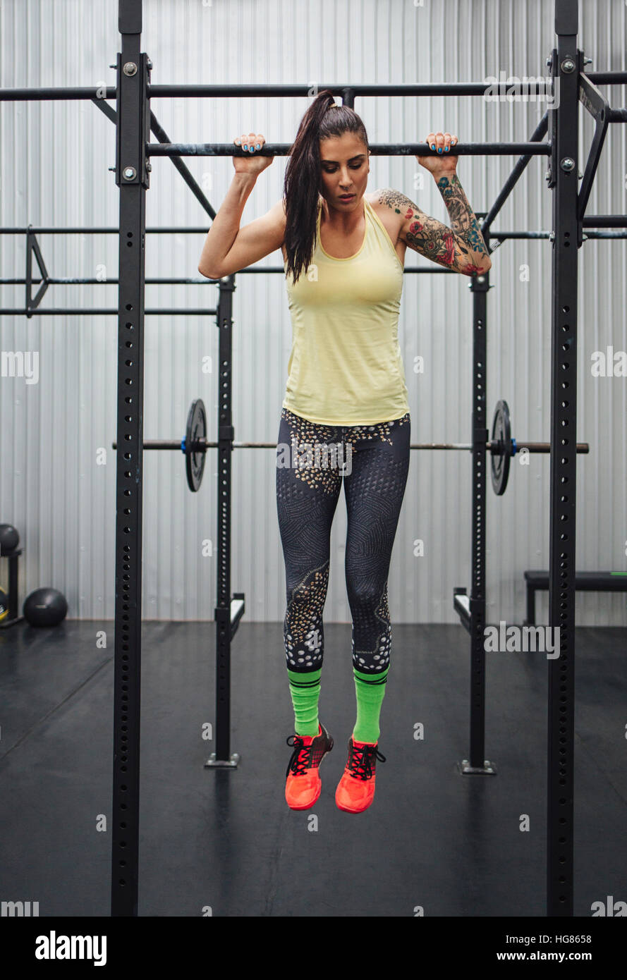 Woman exercising on monkey bars in gym - Stock Image