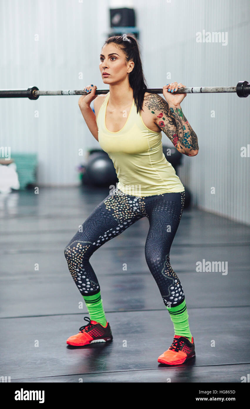 Athlete weightlifting with barbell in gym - Stock Image