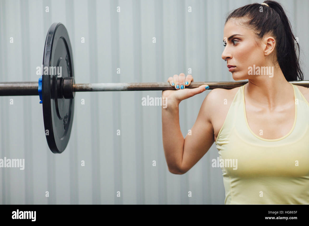 Athlete looking away while weightlifting with barbell in gym - Stock Image