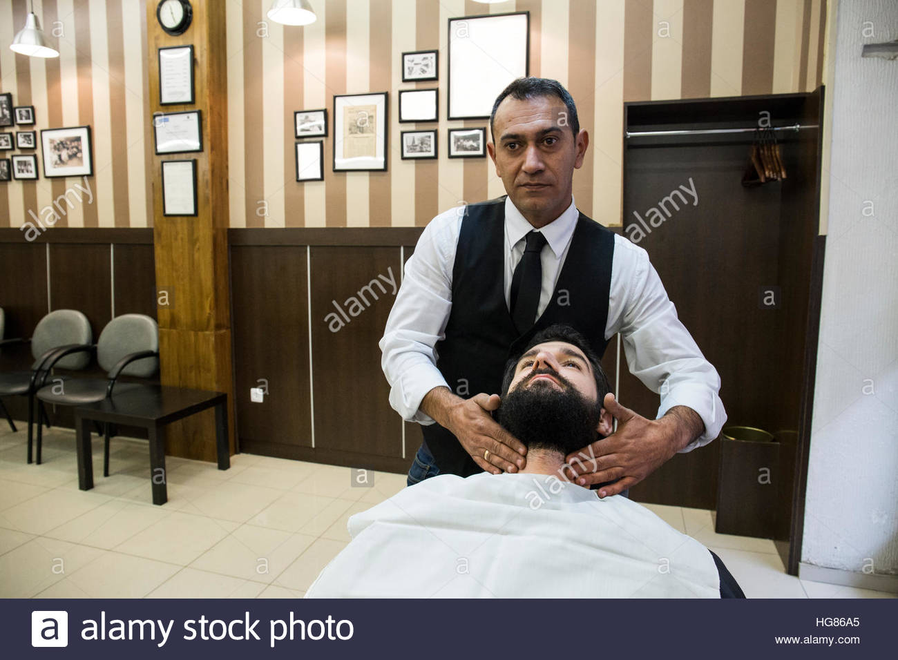 Barber doing facial massage to man in shop - Stock Image