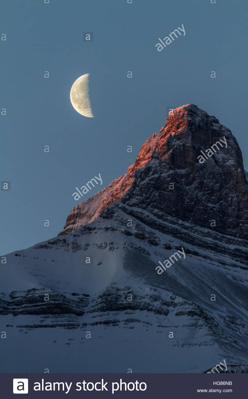 A half moon begins to set behind a towering, snow-covered mountain in Canmore, Alberta, Canada - Stock Image