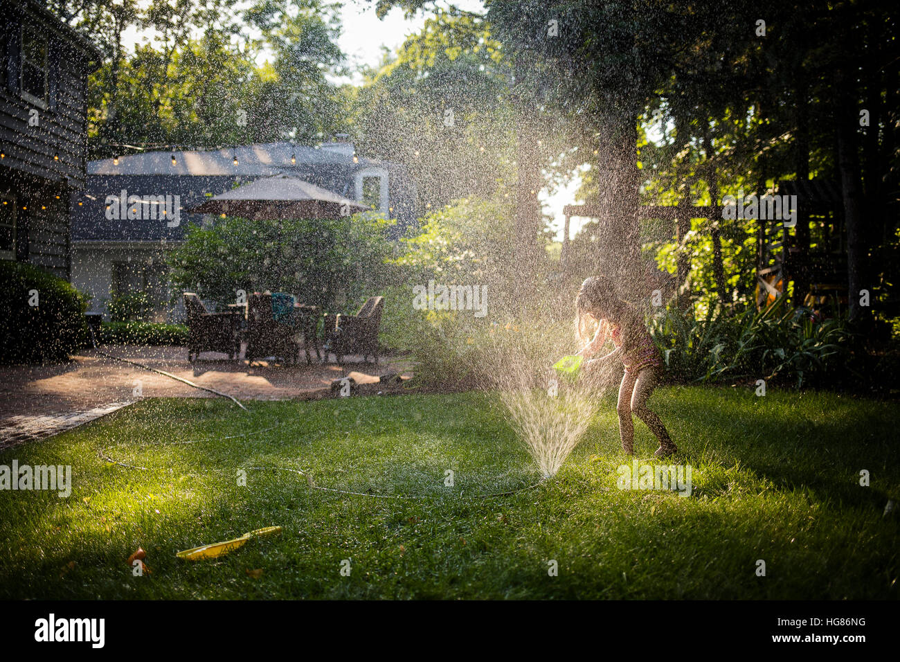 Happy girl in swimwear playing with sprinkler in backyard - Stock Image