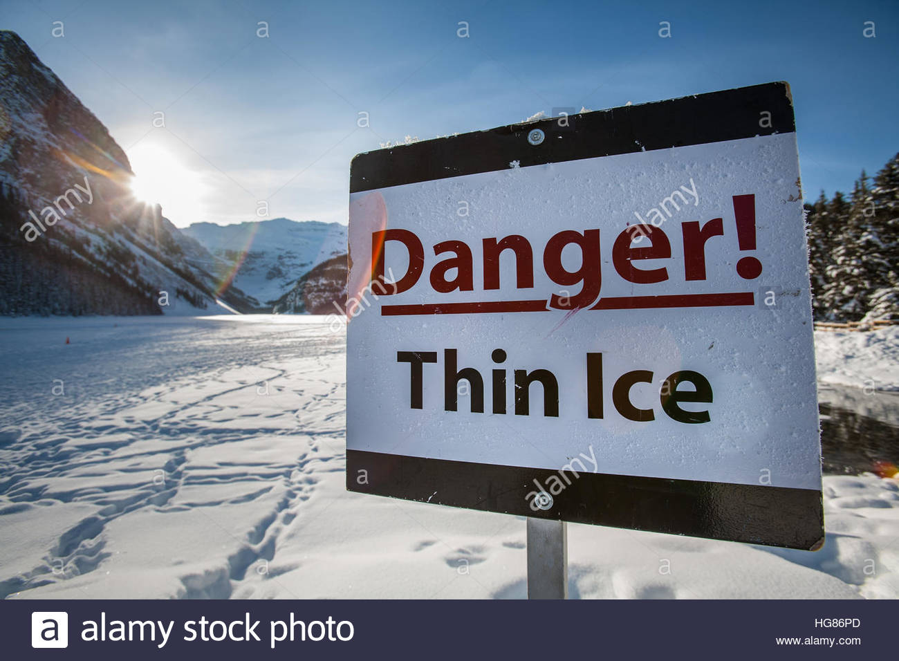 A 'Danger! Thin Ice' sign stands in front of frozen over Lake Louise during a sunny winter day - Stock Image