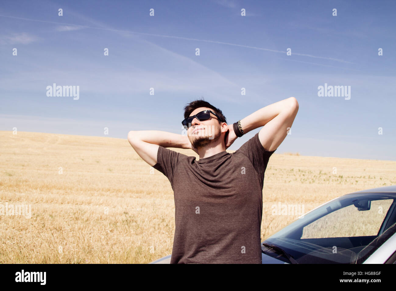 Young man enjoying the sun in a break of his road trip - Stock Image