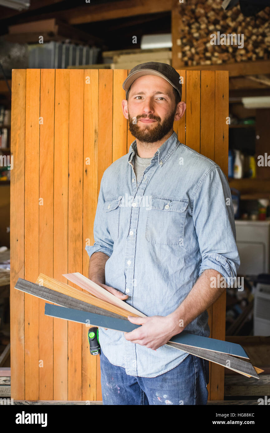 Portrait of man holding planks while standing against wood in workshop - Stock Image