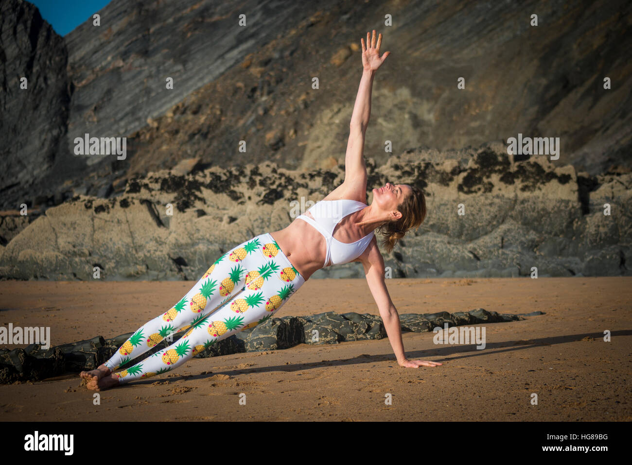 woman doing side plank yoga pose at the beach - Stock Image