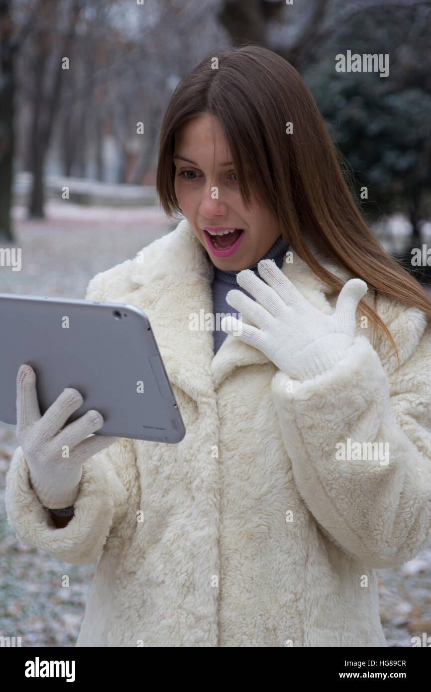 young girl in the park looking at tablet - Stock Image