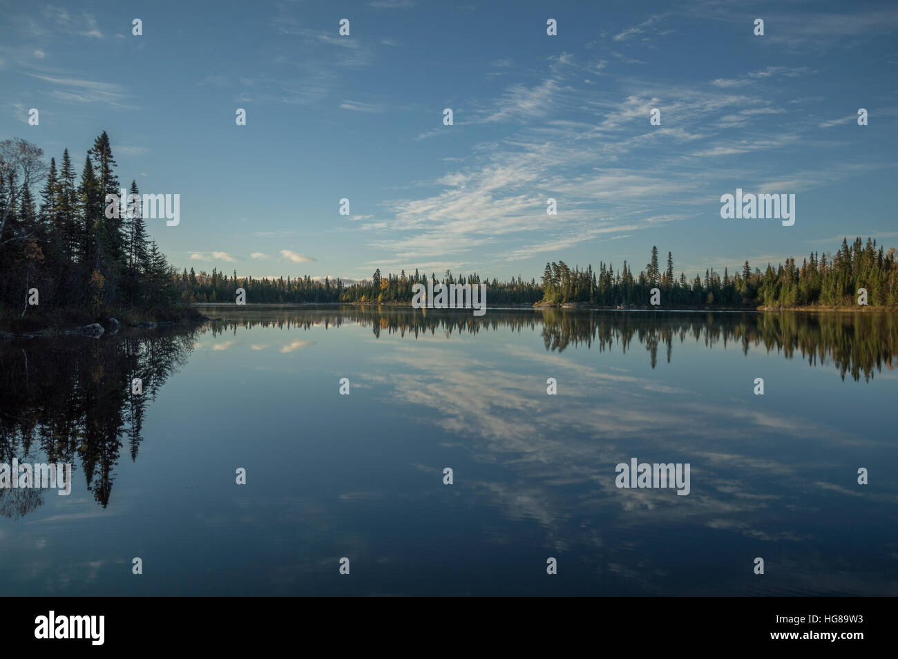 Dead calm lake in early morning with reflections of conifers and wispy cirrus clouds - Stock Image