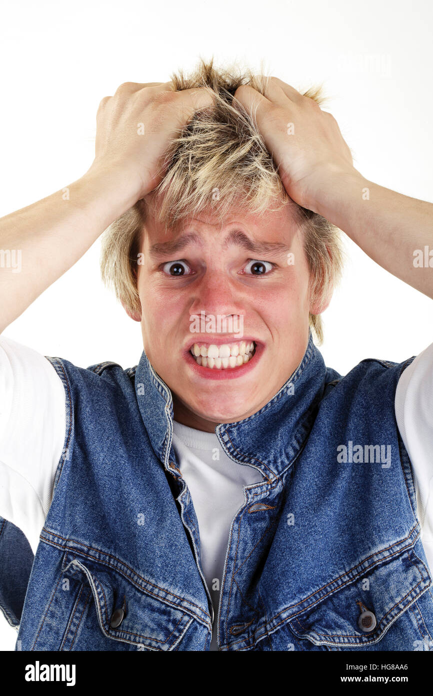 Young man running his hands through his hair looking worried - Stock Image