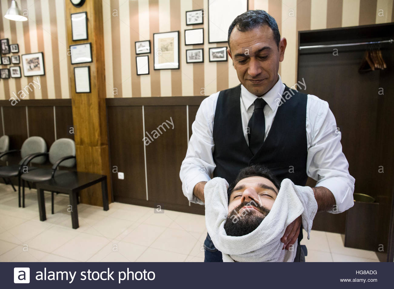 Barber drying man's face in shop - Stock Image