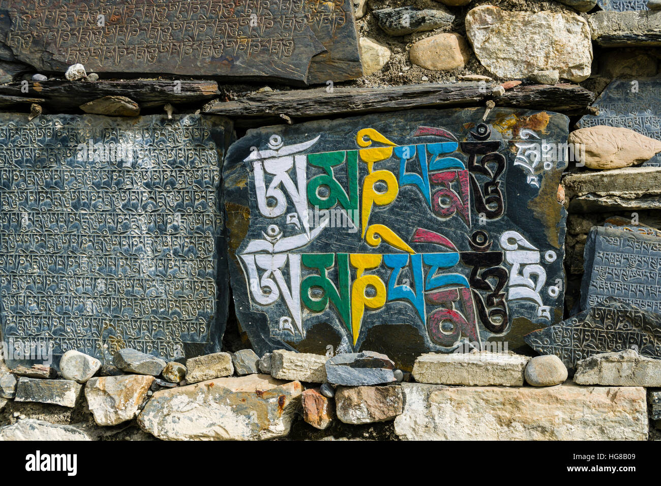 Mani stones with engraved colorful tibetan mantra at a wall, Manang, Manang District, Nepal - Stock Image