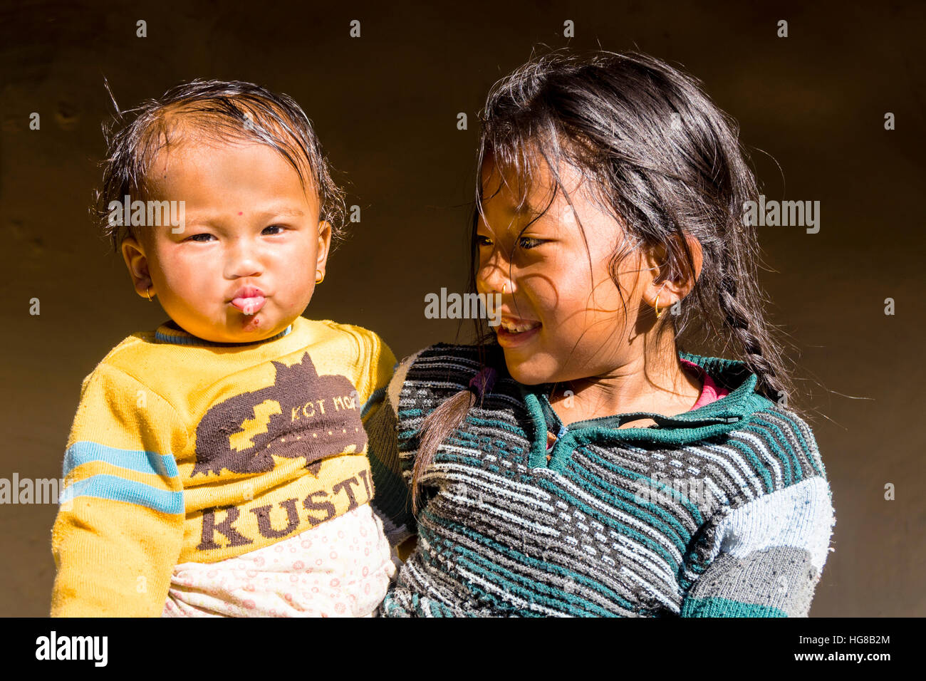 Portrait, young girl hugging even younger boy, Ghandruk, Kaski District, Nepal - Stock Image