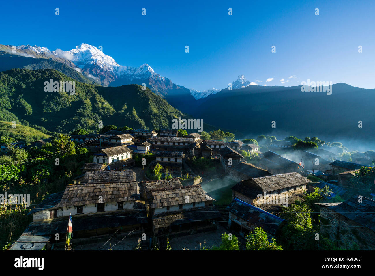 View on the village, back the mountains Annapurna South, left, Himchuli, mid, and Machapuchare, right, Ghandruk, - Stock Image