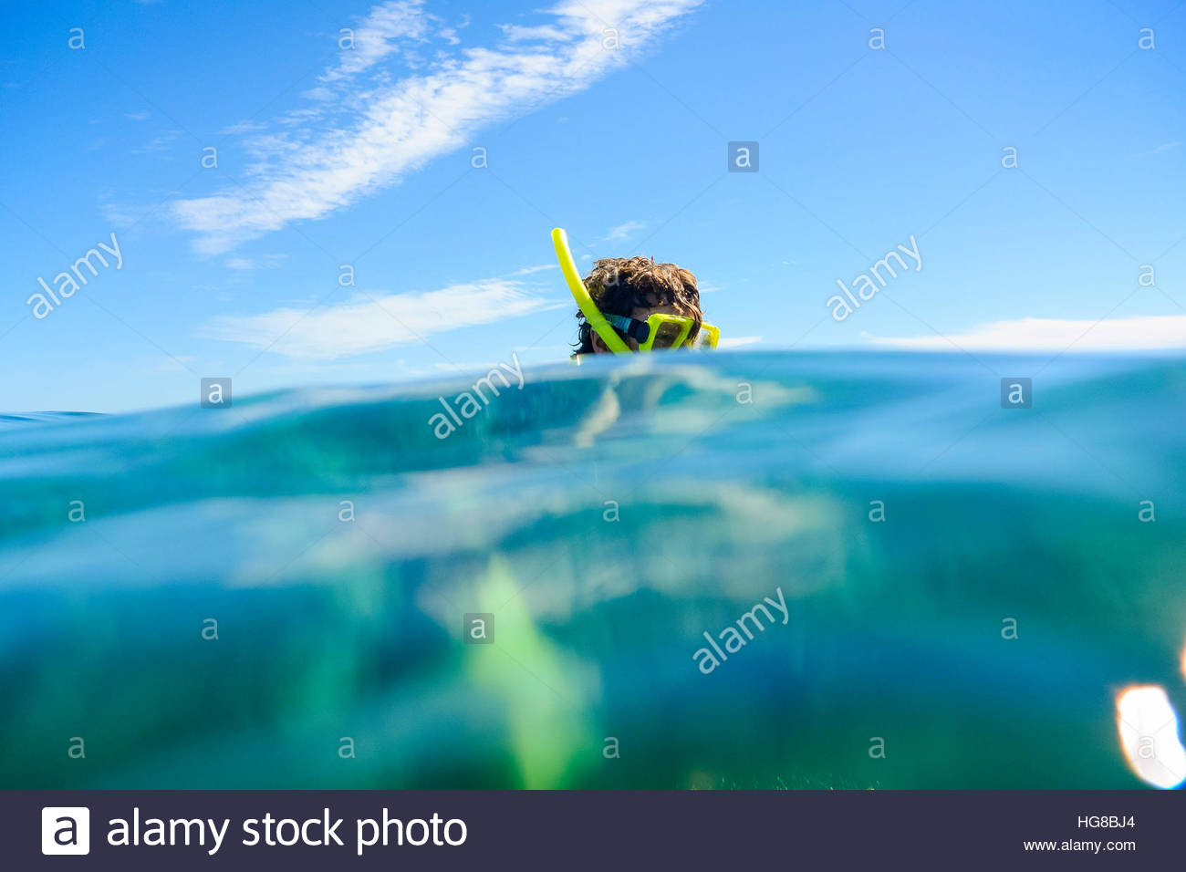 Man snorkeling in sea against blue sky on sunny day - Stock Image
